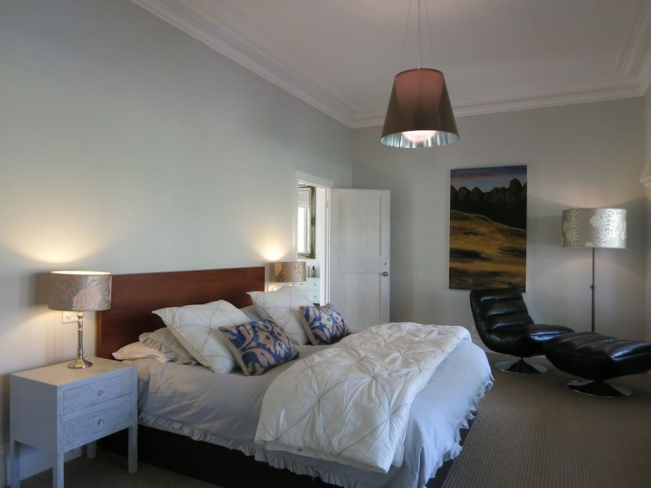 The master bedroom is huge with a king size bed with beautiful linen.