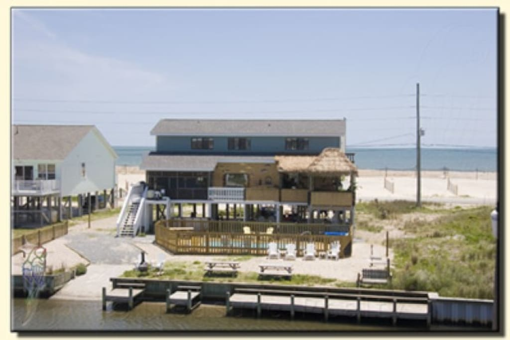 older image-not as large tiki bar area now. View is from from canal, between 2 beach access paths,