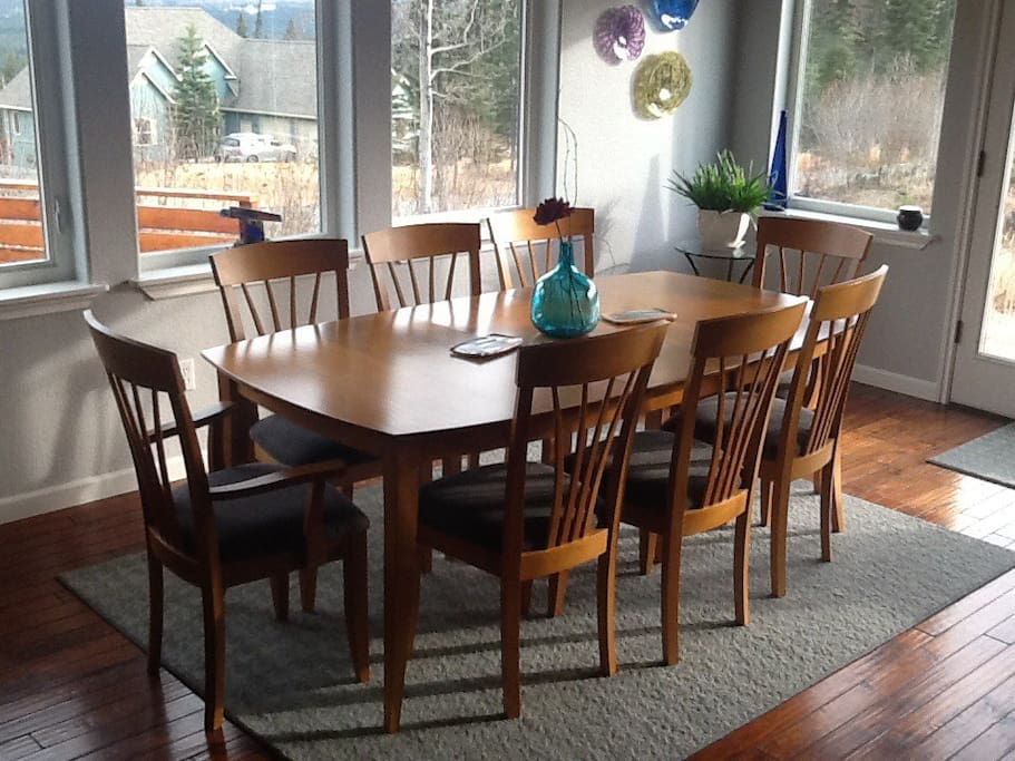 Dining table seats 8 and includes view of Kenai Mountains across the Kenai River and Kenai Wildlife Refuge. Off to the right are windowed doors for easy access to the yard.
