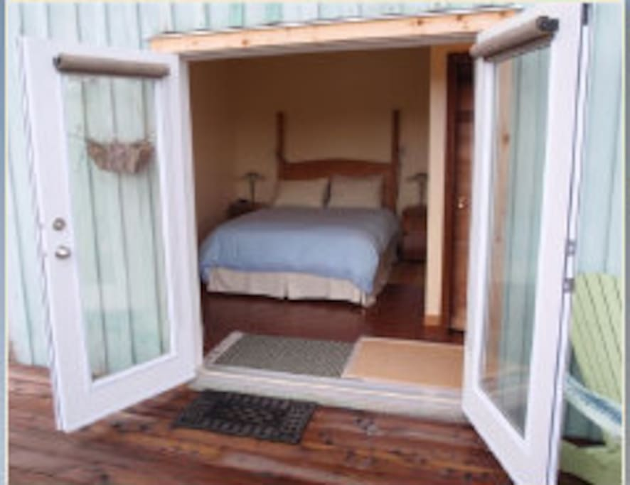 Double poster bed with view through French doors