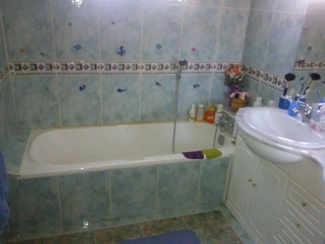 Salle de bain avec baignoire commune et deux vasques, l'une étant destinée aux invité(e)s