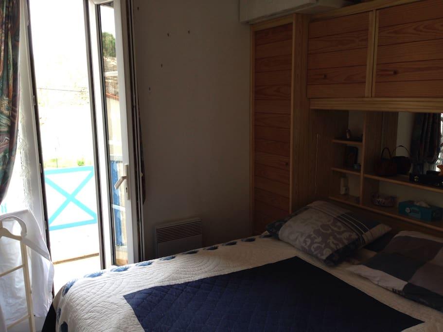 La chambre, lit pour deux personnes, avec son balcon privatif.
