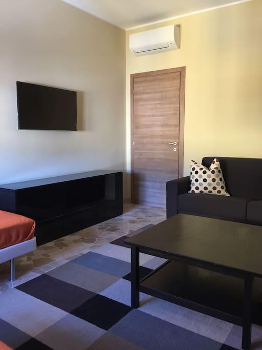 Ingresso soggiorno con divano letto due posti e TV