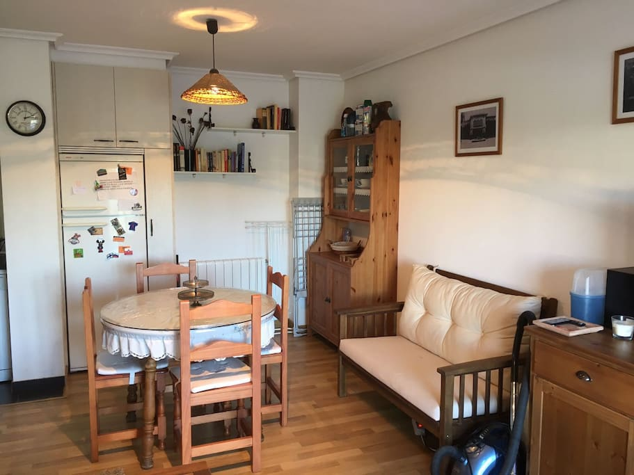 Salón con mesa extensible, sofá, sillones, cajonera y televisión