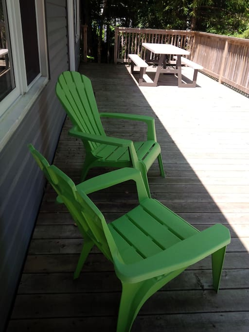 Front deck with picnic table and lounge chairs.