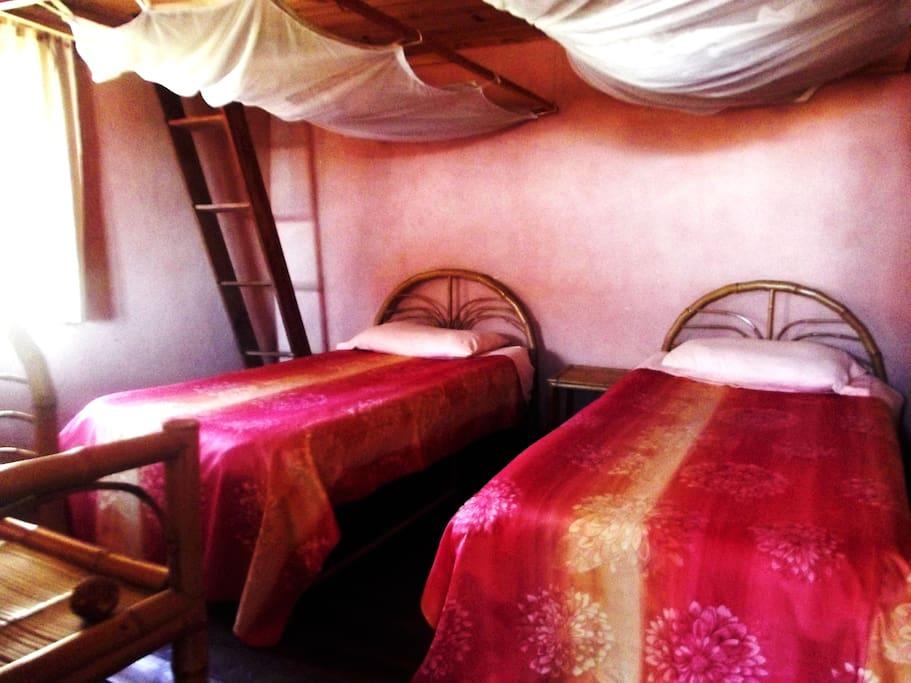 Chambre avec deux lits simples avec des moustiquaires.