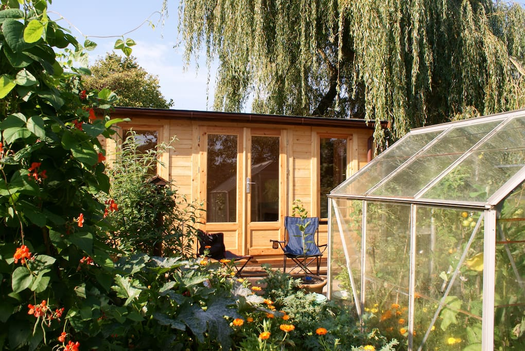Log cabin with double futon looks onto veggie patch