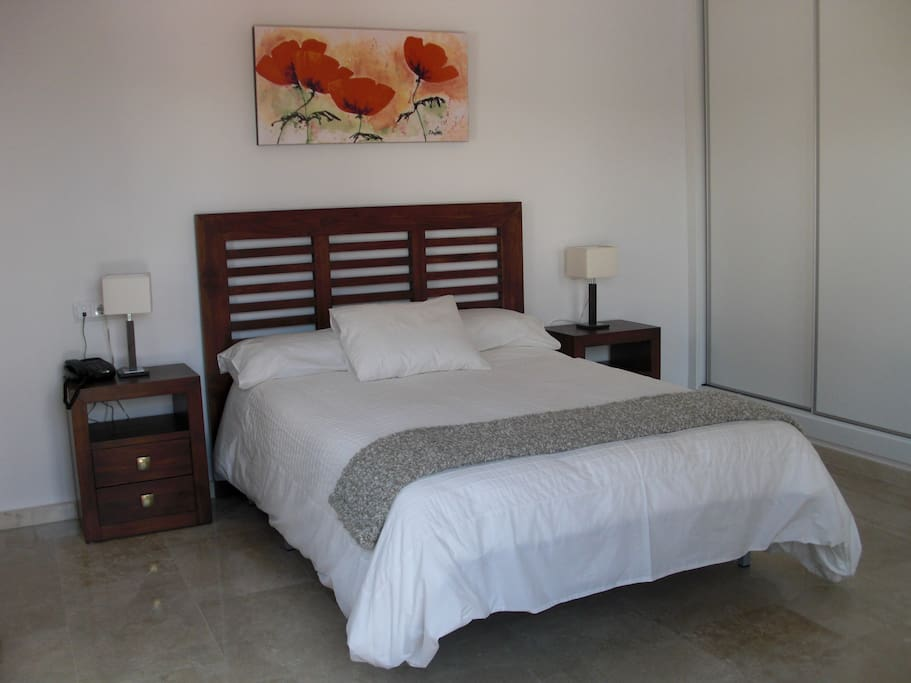 The master bedroom, with a king size bed and patio doors that open directly onto the pool area.