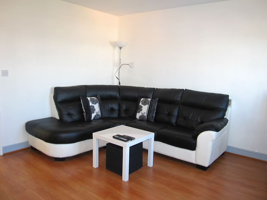 Spacious and bright living room with comfortable L shaped leather sofa