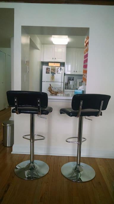 Bar counter stools facing kitchen.