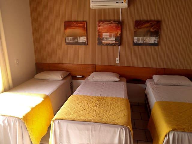 Quarto com 3 camas de solteiro, ar condicionado, tv e guarda roupa.