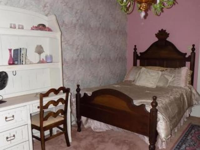 Lighted desk & Chair. Antique & ornate full sized bed.