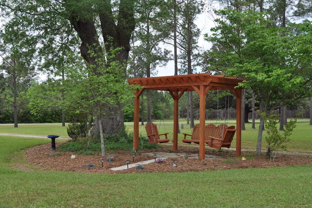 Our pergola with a 3 person swing and 2 single swings under a 100 yr old live oak tree.