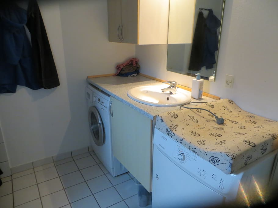 Badeværelse med vaskemaskine, tørretumbler samt pusleplads.