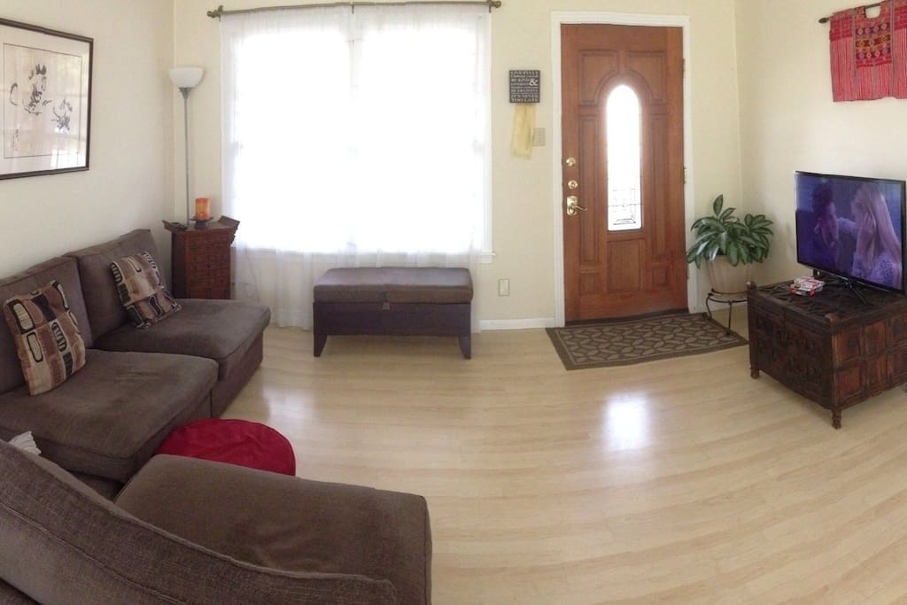 The living room with hardwood floors and comfy furniture.
