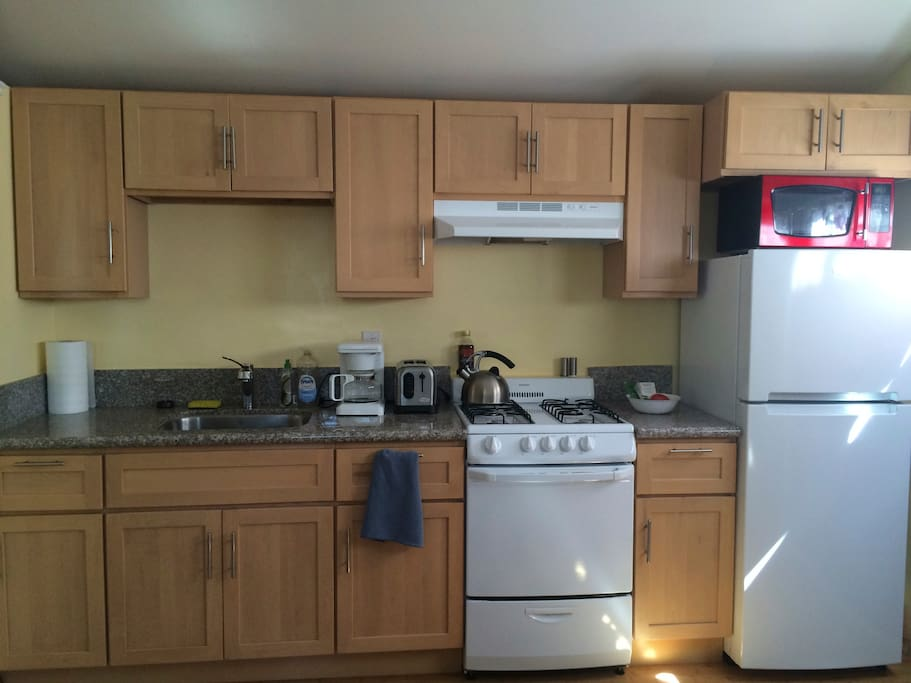 Full kitchen with with coffee maker, toaster, stove, microwave, pots, pans, and dishes.
