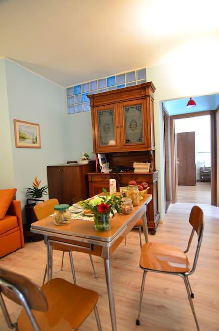 -ENG: living room with extendible table, old cupboard, and build in washing machine -ITA: soggiorno con tavolo allungabile, antica credenza e lavatrice incassata.