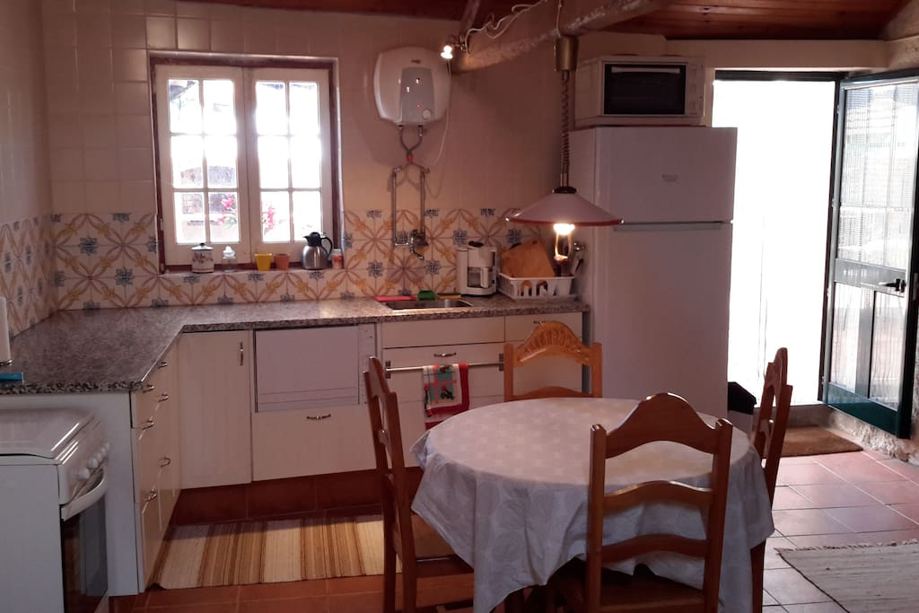 The kitchen with a big, new fridge. A gas stove and a small dishwasher. Electric hot water heater above the sink.The door leads out to the back yard.