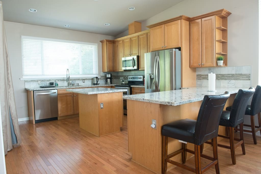 Full-sized kitchen with modern stainless steel appliances: fridge, icemaker, dishwasher, stove, microwave, oven