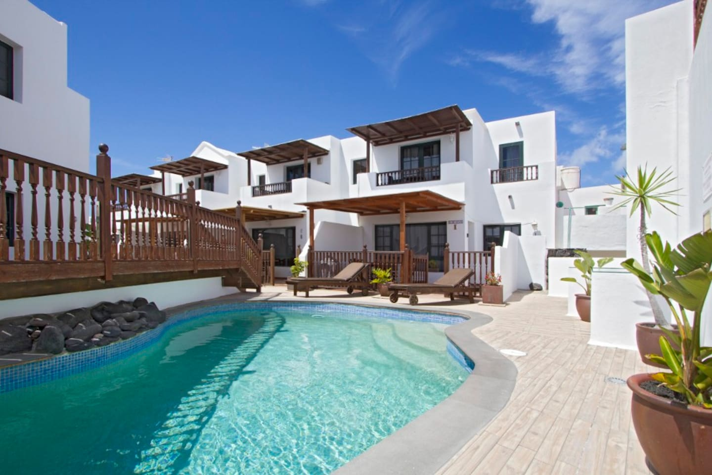 Pool area, with solar heated pool and sunbeds. Viewing the front of the properties.