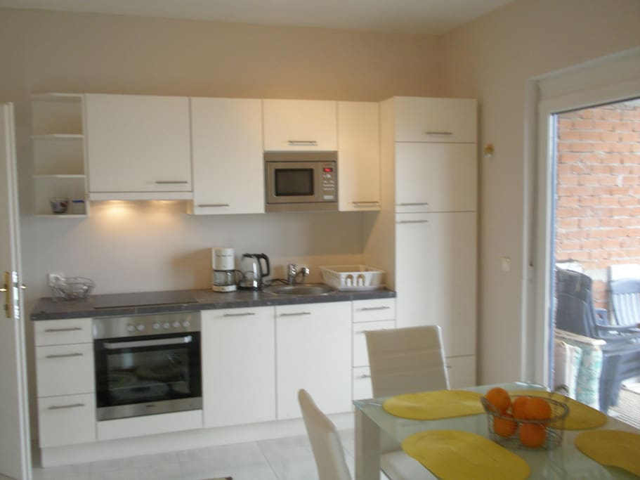 KitKitchen with fridge-freezer, electric stove with oven, microwave and sink