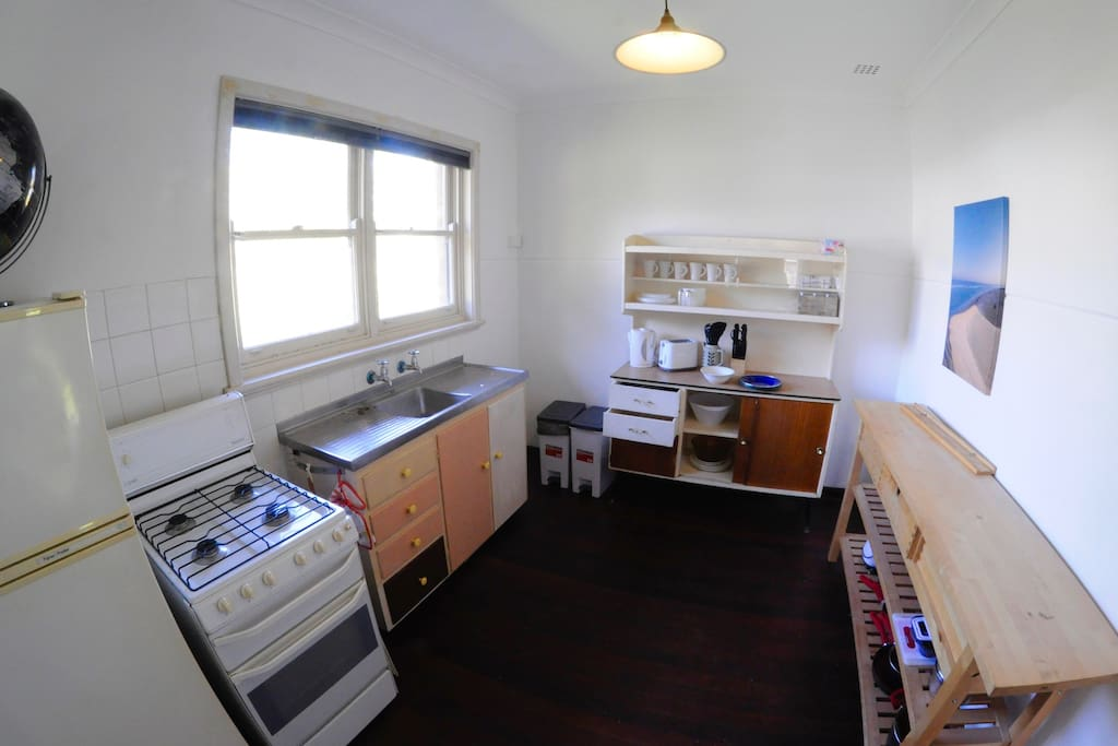 the kitchen with a view of the tree-lined street. Gas stove, refrigerator, microwave, kettle and toaster.
