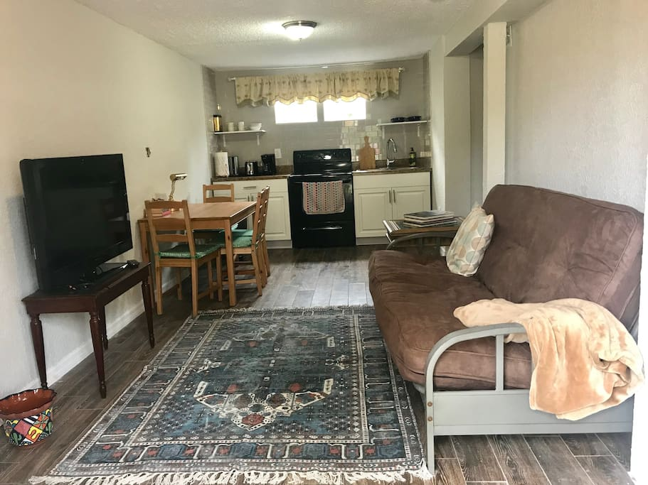 Opens up into a living room with a tv, 4 person kitchen table, full kitchen.. full stove and fridge included and a futon that can serve as a couch or a double/full bed that sleeps two people.