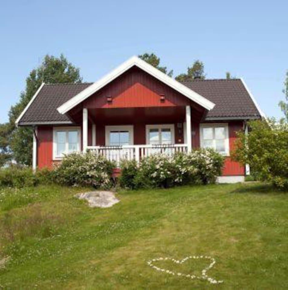 Blomsterhaugen , koselig rødmalt bestemorhus i skogkanten.