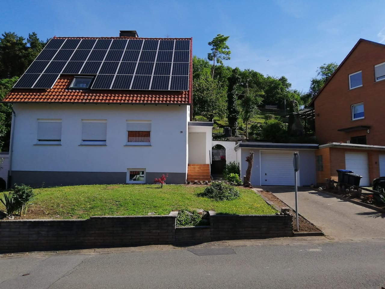 Hausfront im Sonnenschein mit PKW-Stellplatz