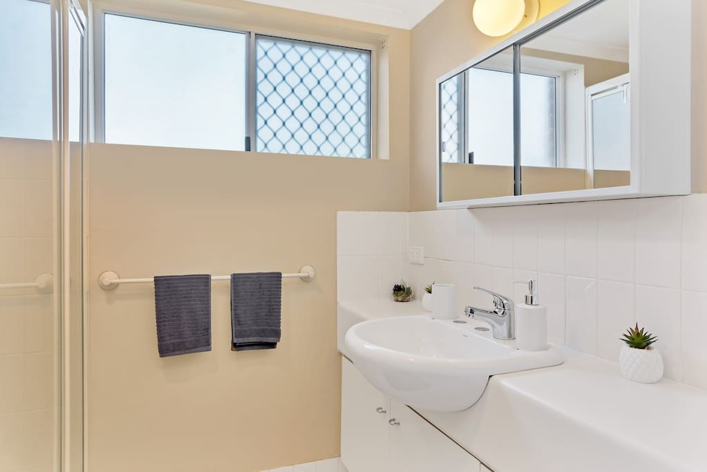 Clean, modern bathroom with large shower + laundry