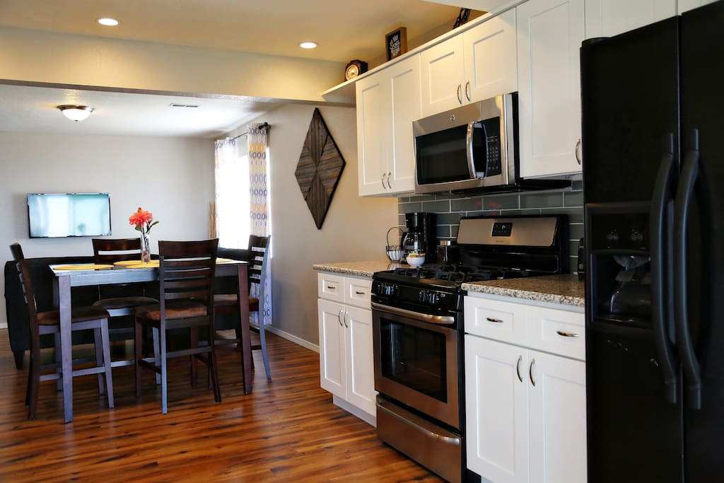 Open-concept kitchen and dining features a gas range and ample space for 4.