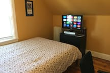 Queen bed with Apple TV and work desk