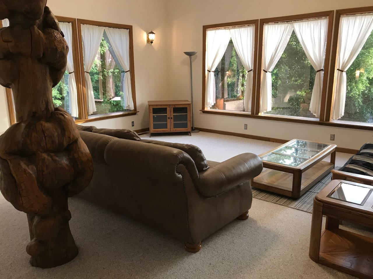 2nd level spacious living room with views of inlet and custom burl log hand-sanded by owner