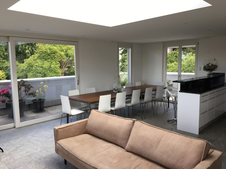 Huge living space on the top floor with big kitchen, sofa and table - open the big window slide doors and you feel like sitting outside.
