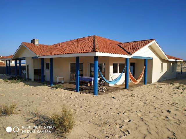 Maison en bord de mer, les pieds dans le sable