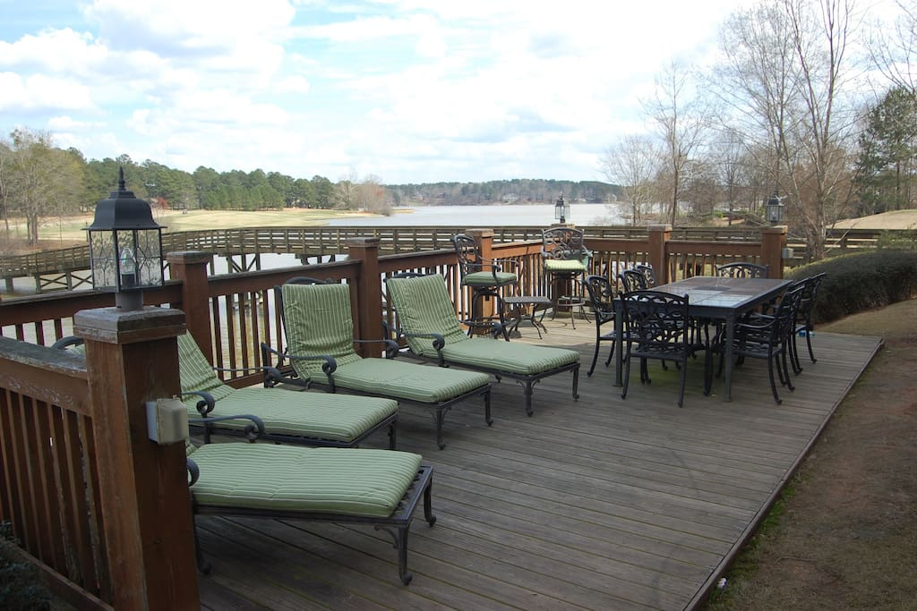 Private deck with table and lounge chairs overlooking the lake.