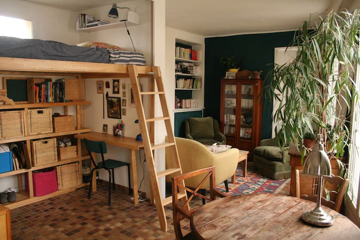 the loft-bed in the living room, dining table in the front and the living room