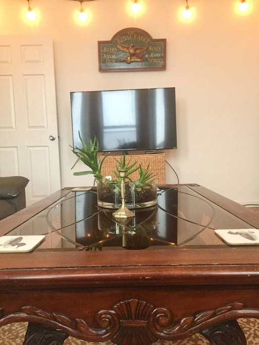 Mahogany and glass living room table with succulent bowl. My antique tavern sign is above the tv -- you're welcome to watch.