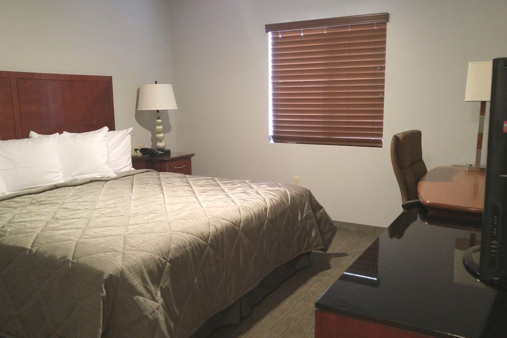 """Separate bedroom area includes king sized bed, 40"""" flat screen television, desk area and closet"""