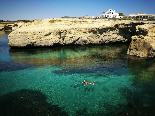 La proprietaria che nuota felice nelle acque cristalline, con la casa sullo sfondo