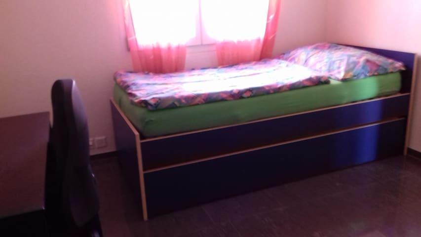 helles Zimmer mit Bett und Pult