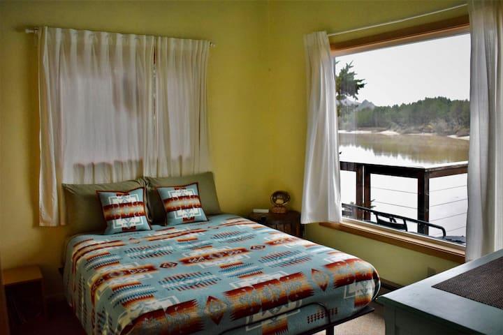 Southwest bedroom; adjustable queen bed, view of three rocks through picture window