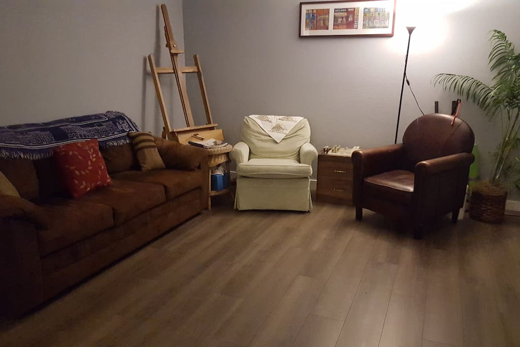 Living room- with two chairs, couch, 3 end tables, chess board, & art easel.