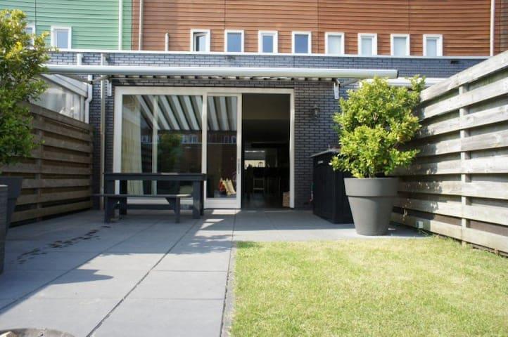 Backyard, looking toward sliding glass door in living room. Sun shade for enjoying the bright Dutch sunshine while outdoors!