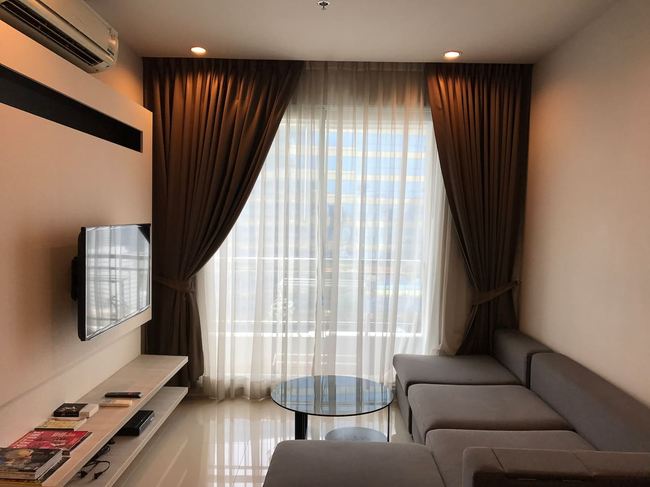 Spacious living room, with coffee table, good clean aircon, blackout curtains, polished flooring, balcony.
