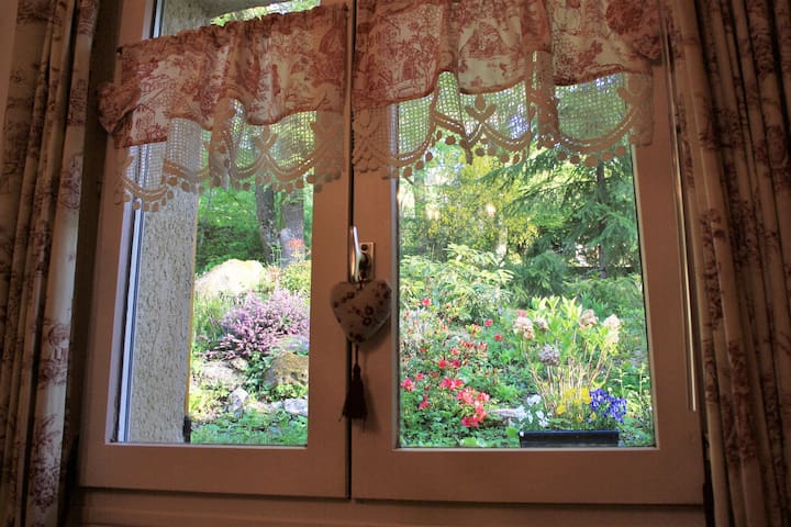 Fenêtre donnant sur le jardin au printemps
