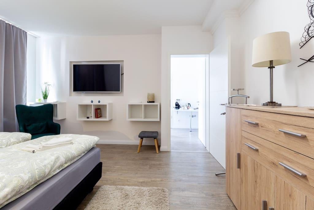 Blick in das Schlafzimmer und zum Wohnzimmer des zwei Zimmer Apartments