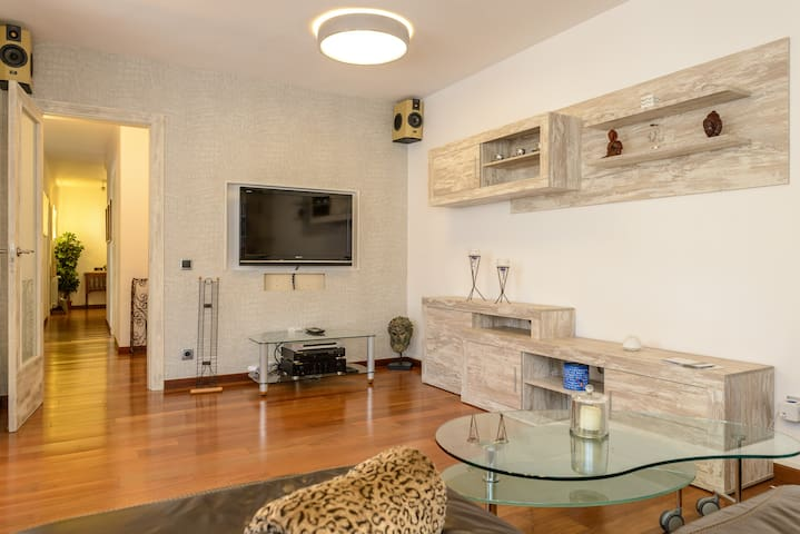 Sala de estar, con tv, satélite, equipo de música Marantz, altavoces surround, mesa de cristal de diseño y lámpara de techo italiana con luz cálida