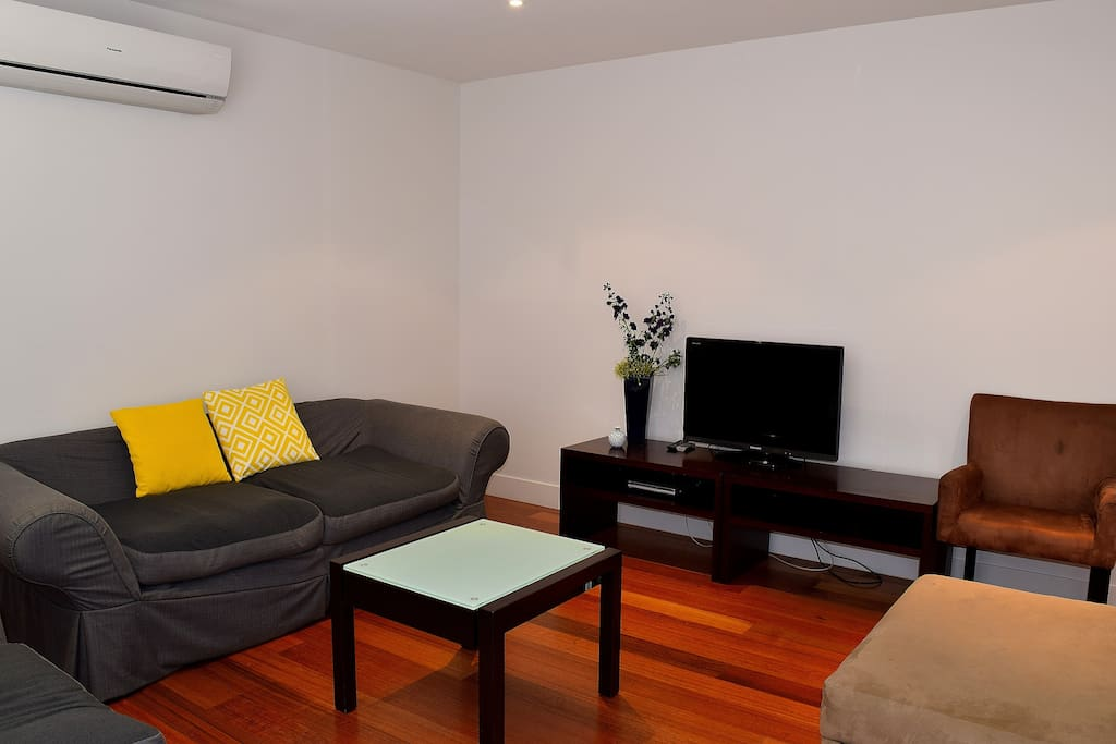 Spacious lounge, plenty of seating, TV and light. Vertical blinds open up for access to courtyard.
