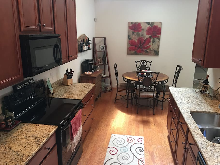 Well-appointed kitchen with granite countertops, microwave, dishwasher